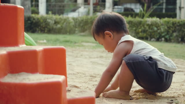 little baby boy playing with sand - sand pit stock videos and b-roll footage