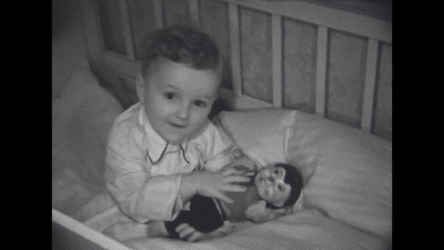 Little baby boy taking a bath sitting in the bed having a puppet of the Meckie figure in his hands