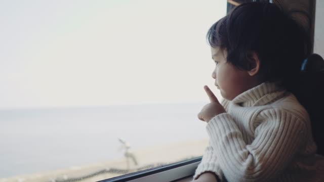 窓の外を見て電車の中で旅行する小さな赤ちゃん男の子。 - son点の映像素材/bロール