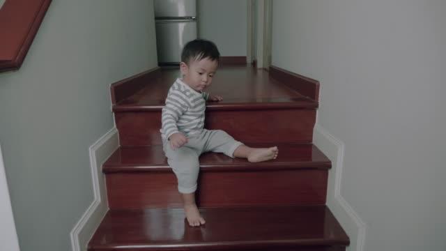 小さな男の子は家の階段を歩いてします。 - 階段点の映像素材/bロール