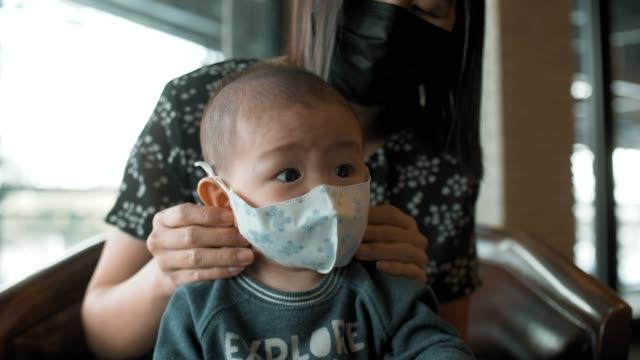 kleines baby junge (2-5 monate) trägt verschmutzung masken - männliches baby stock-videos und b-roll-filmmaterial