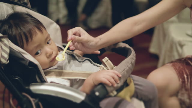 stockvideo's en b-roll-footage met kleine baby eten in baby wandelwagen. - supersensorisch