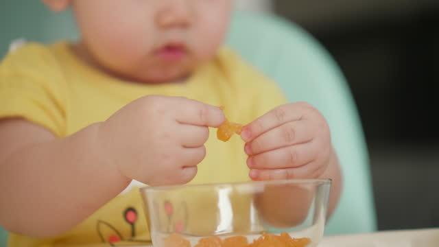 stockvideo's en b-roll-footage met weinig baby die weinig stuk fruit eet - one baby boy only