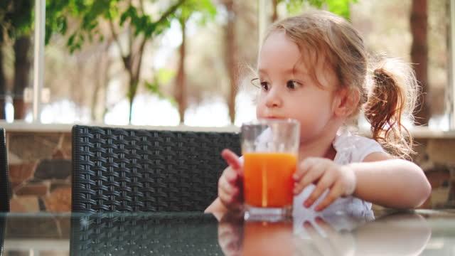little baby girl drinking orange juice - juice drink stock videos & royalty-free footage