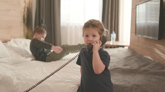liten flicka som håller telefonmottagare på hotellrum medan bror ligger på sängen i bakgrunden - liquid crystal display bildbanksvideor och videomaterial från bakom kulisserna