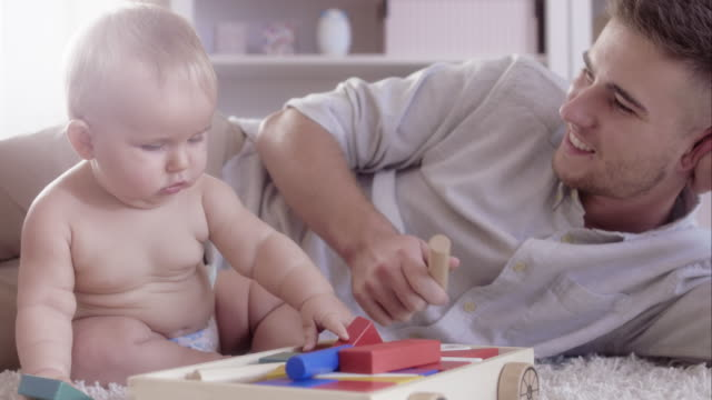 little baby girl playing with her father - genderblend stock videos & royalty-free footage