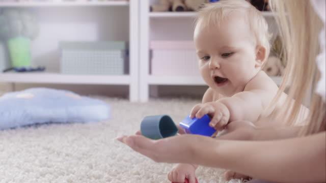 Pequeño bebé niña jugando con su madre