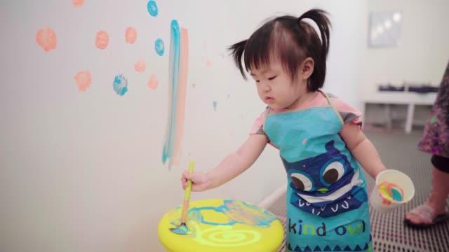vídeos y material grabado en eventos de stock de little baby girl playing with paints - sucio