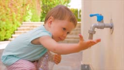 Little baby girl playing with water. Toddler playing with water flowing from tap. Kid holding empty plastic bottle near tap. Water problems background. Fresh water problems. Kindergarten concept