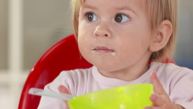 vidéos et rushes de hd: petit bébé fille souriant pour plus de nourriture - 18 23 mois