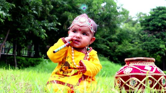 vidéos et rushes de petit bébé krishna avec la flûte et makhan matki dans la nature - vidéo portrait