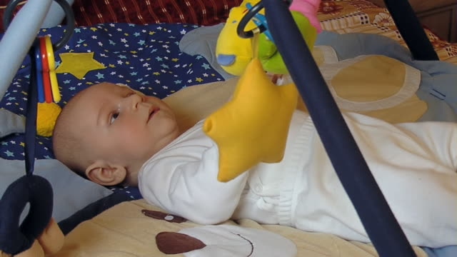 Little baby plays with hanging toys