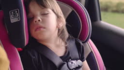 Little baby sleeping in safety carseat.