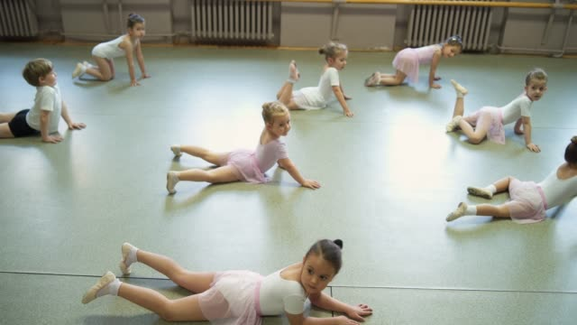 little ballet dancers stretching before ballet class - barre stock videos & royalty-free footage