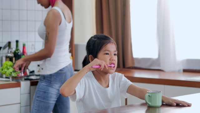 little beautiful girl brushing teeth. tattooed mother at home with daughter.spending time with her cute baby at home.healthy concept.day in the life of a family - toothpaste stock videos & royalty-free footage