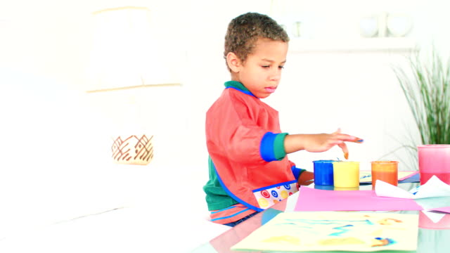 hd: little biracial boy finger painting - finger painting stock videos and b-roll footage