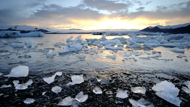 little blocks of ice on the shore at sunset. jokulsarlon, iceland. - northern europe stock videos & royalty-free footage