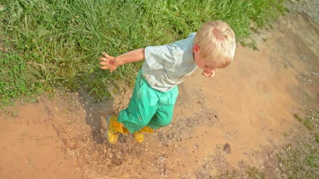 雨の後、日差しの中で泥だらけの水たまりにジャンプ アップとダウン slo mo 小さな金髪の男の子 - tシャツ点の映像素材/bロール