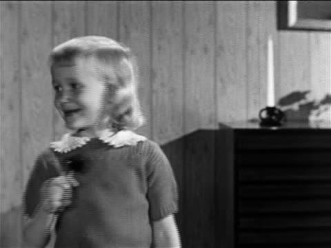 b/w 1957 little blond girl standing in living room licking lollipop / educational - lollipop stock videos and b-roll footage