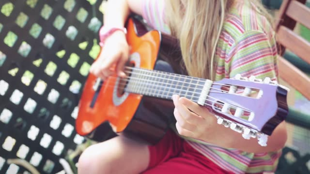 Little blonde girl playing the guitar