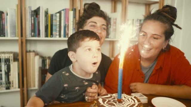 little blåser en födelse ljus med sina hbt föräldrar (slow motion) - party social event bildbanksvideor och videomaterial från bakom kulisserna