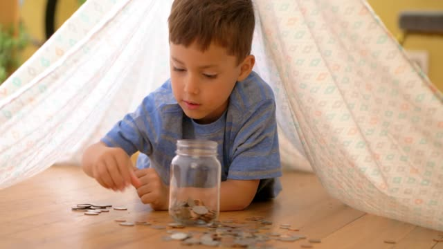 little boy adding coins to jar. - piggy bank stock videos & royalty-free footage