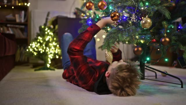 little boy adjusting the christmas tree - lying on back stock videos & royalty-free footage