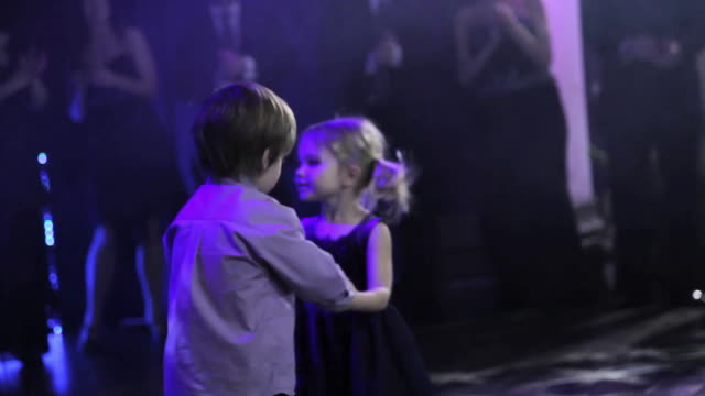 vidéos et rushes de little boy and girl dance in middle of dance floor, ringed by clapping dancers - petits garçons