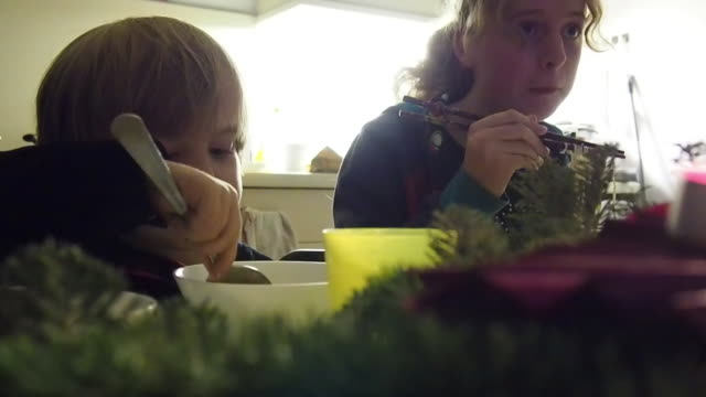 vidéos et rushes de little boy (4 years) and girl (13-14 years) eating asian spaghetty soupe. there is christmas decoration on the table (pine branches). - 14 15 years