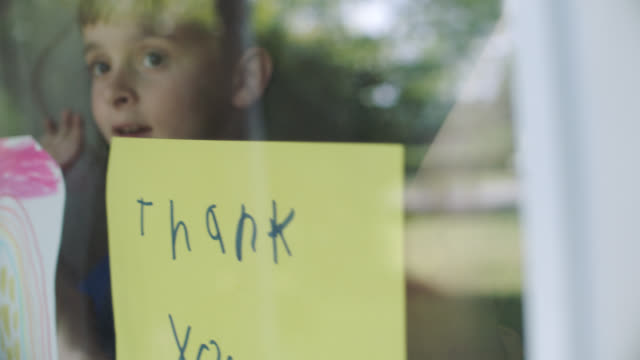 slo mo. little boy and girl hold up thank you signs and drawings. - healthcare worker stock videos & royalty-free footage