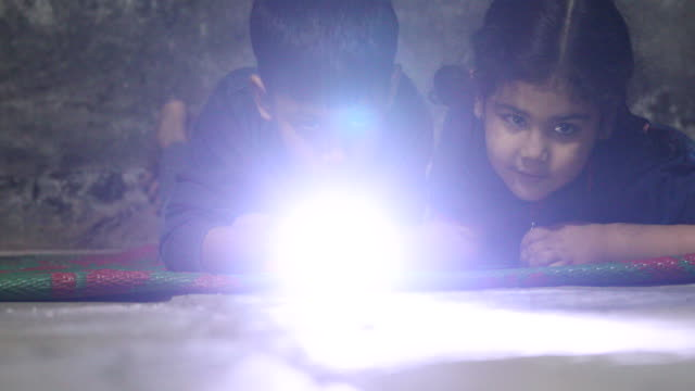 little boy and girl holding a pocket torch light and searching in the darkness.