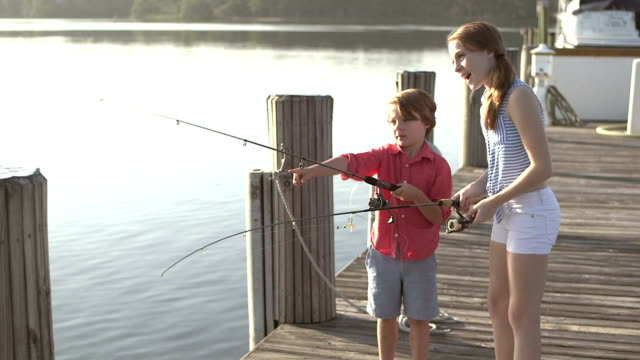 Little boy and his big sister with fishing rods on dock