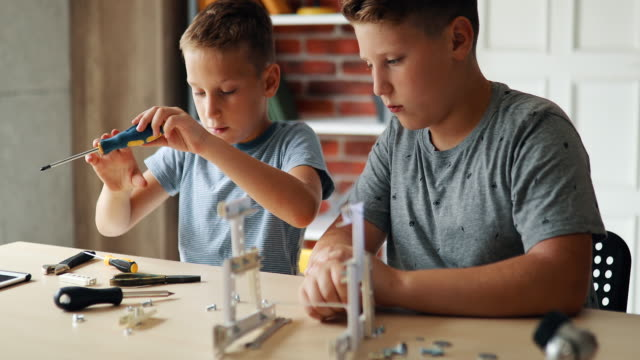 little boy and his brother making a robot for school science project - school science project stock videos & royalty-free footage