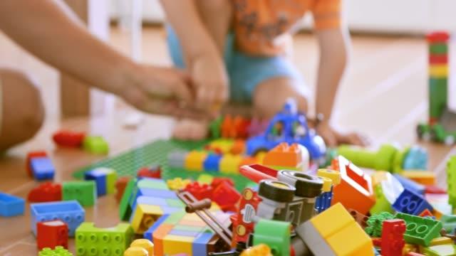 vídeos de stock, filmes e b-roll de menino e seu pai a construir com tijolos de plástico - bloco de construção