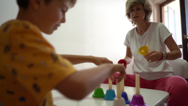 little boy and his female therapist having fun with multi colored bells during occupational therapy at rehabilitation center - invisible disability stock videos & royalty-free footage