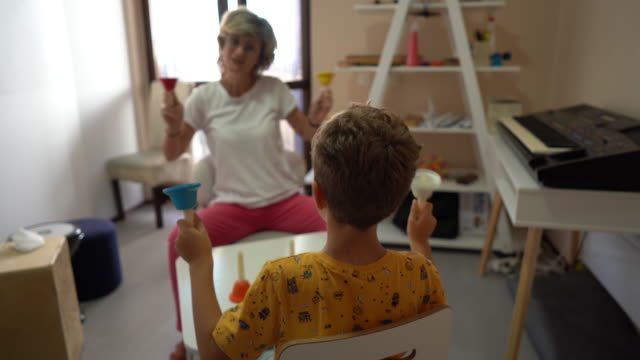 little boy and his female therapist making music with multi colored bells during occupational therapy at rehabilitation center - invisible disability stock videos & royalty-free footage