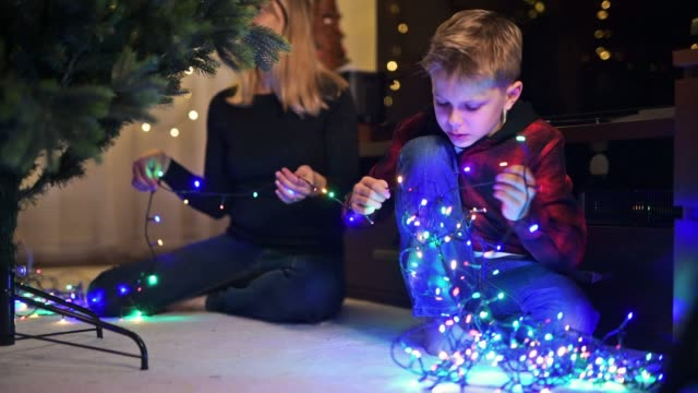 little boy and his mother preparing christmas lights on christmas tree - imgorthand stock videos & royalty-free footage