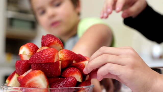little boy and his sister piling strawberries - mixing bowl stock videos and b-roll footage