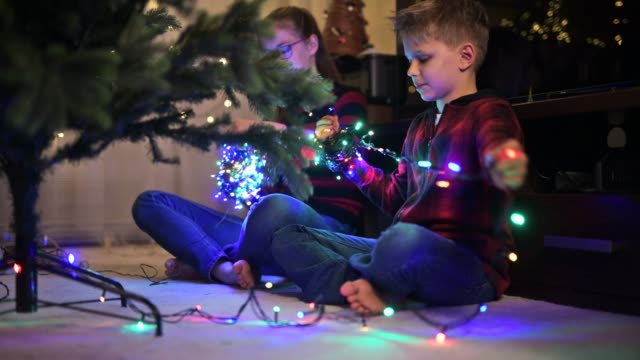 little boy and his sister preparing christmas lights on christmas tree - imgorthand stock videos & royalty-free footage