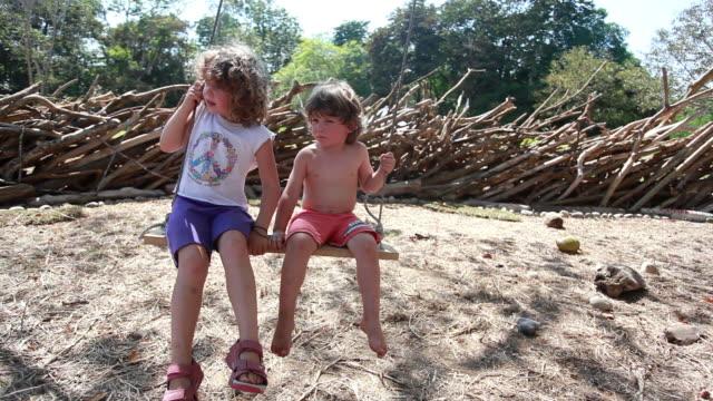 vídeos de stock e filmes b-roll de ms little boy and little girl on swing / montezuma, nicoya peninsula, costa rica   - equipamento de parque infantil