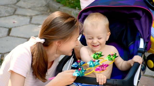 vídeos y material grabado en eventos de stock de pequeño niño y madre jugando en el parque en verano - cochecito de bebé