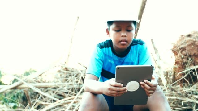 少年アジア エンジニアの帽子を使用してデジタル テーブル、コンセプト エンジニアの夢 - 通信点の映像素材/bロール