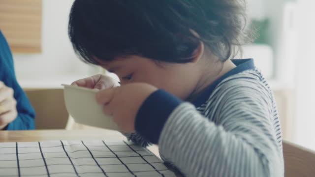 vídeos de stock, filmes e b-roll de rapaz pequeno em casa que come o pequeno almoço na cozinha junto - comida de bebê