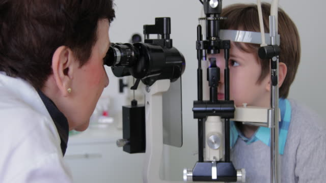 little boy at ophthalmologist office - lens optical instrument stock videos & royalty-free footage