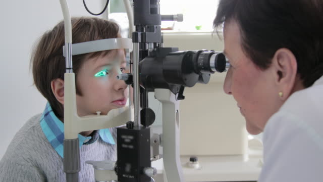 little boy at ophthalmologist office - optical instrument stock videos & royalty-free footage