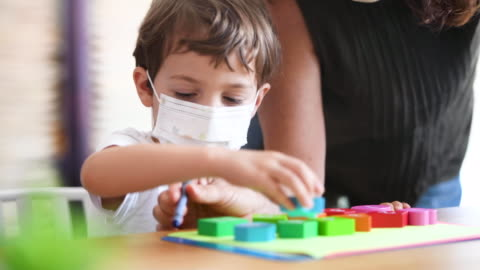 little boy at pre school classroom wearing a protective face mask - elementary school stock videos & royalty-free footage