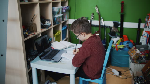 little boy attending to online school class from his room. - studio camera video stock e b–roll