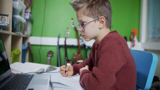 彼の部屋からオンライン学校のクラスに出席する小さな男の子。 - 勉強する点の映像素材/bロール