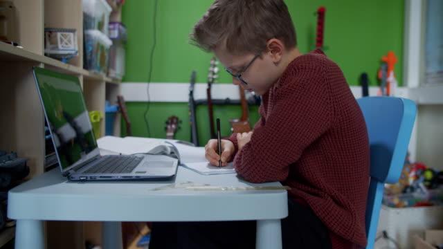 stockvideo's en b-roll-footage met weinig jongen die aan online schoolklasse van zijn ruimte bijwoont. - e learning