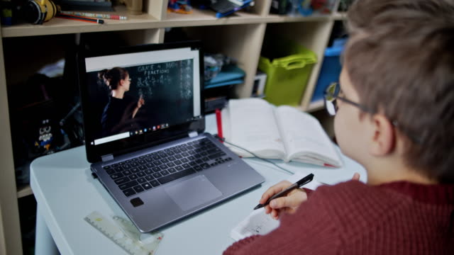 little boy attending to online school class from his room. - insegnante video stock e b–roll